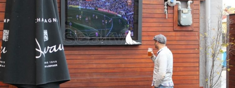 Man watching TV drinking a beer in a beer garden